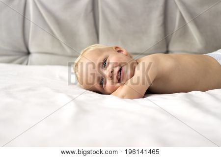 Cute smiling baby boy lying on the bed against the grey background. Copy space.