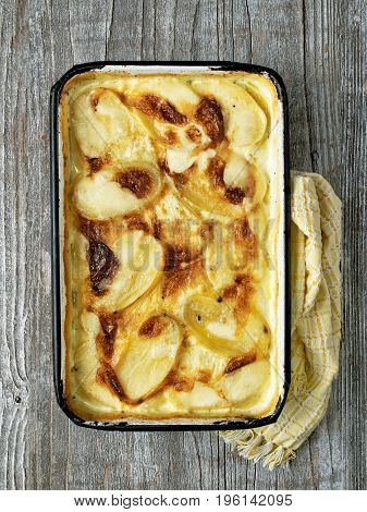 close up of rustic golden scalloped potato gratin dauphinois