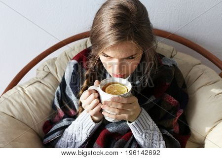 Young ill woman drinking hot tea with lemon while sitting on lounge at home