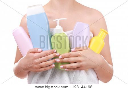 Young woman after shower with cosmetic products on white background