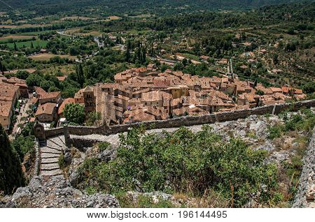 Moustiers-Sainte-Marie, France - July 08, 2016. View of stone staircase, roofs and belfry in the charming village of Moustiers-Sainte-Marie. Provence region, southeastern France