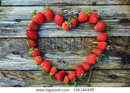 Strawberries on the wooden table. Strawberries heart. Strawberry background. Heart made of strawberries. Fresh Strawberries in the garden. Juicy red berries and leaves on the wooden table. Delicious and healthy food