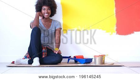 Portrait of a beautiful african american female painter sitting on floor near wall after painting.