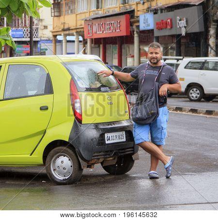 GOA INDIA - March 01 2015: Fashion man posing near Tata Nano