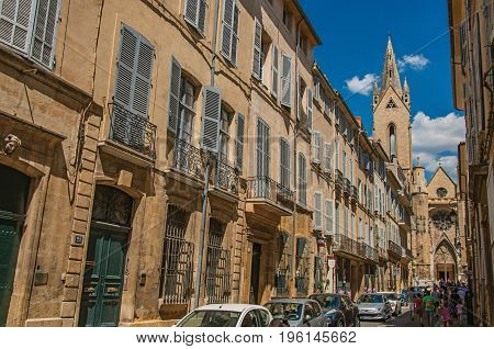 Aix-en-Provence, France - July 09, 2016. Street with buildings and Saint Jean de Malte Church in Aix-en-Provence, a pleasant and lively town in the countryside. Provence region, southeastern France
