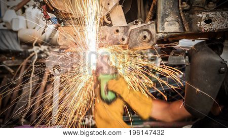 Fire flames are caused by a car mechanic using an electric grinder to grind the iron beam under the car to smooth- Automotive industry and garage concepts.