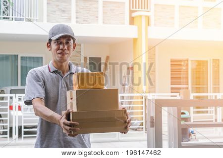 Deliverers in gray uniform stand holding boxes and smiling at customer's front.-Delivery and courier service concepts.
