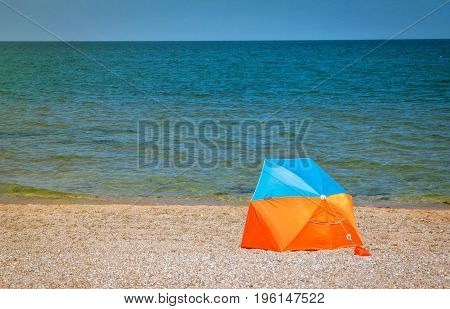 Colorful sun protective portable tent fixed at the beach near the sea in a sunny summer day