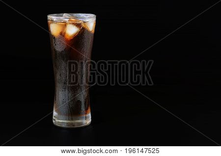 Cola water in a glass with ices over black background industrial food and drink concepts.