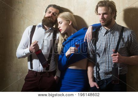 Girl sleeping with glass of liqueur and men with wine bottles. Friends relaxing with alcoholic drinks on beige wall. Alcohol and alcoholism. Friendship and convives. Unhealthy lifestyle and bad habits