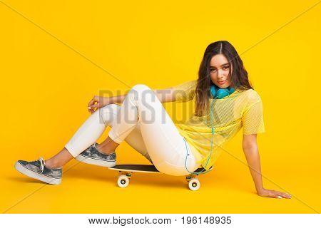 Side view of trendy model in headphones sitting on skateboard posing in studio.