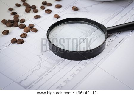 Coffee beans, magnifying glass and financial graph abstract close up for your ideas. Copy space.