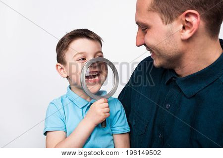 Young boy in blue shirt having fun with magnifier sitting on father's knees.