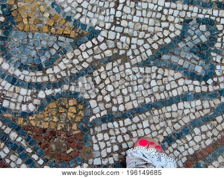 Pedicure girl feet in white sandals with standing on antique mosaic. Archeology style