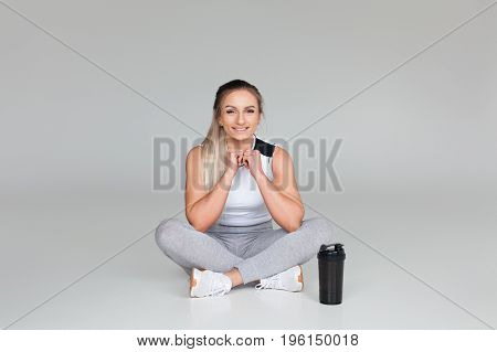 Blonde woman in sporty outfit sitting against gray background with black shaker nearby.