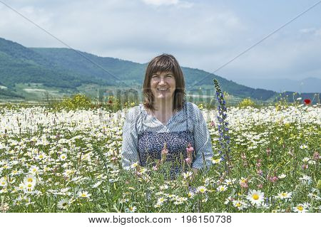Portrait of a happy smiling woman standing on mountain glade full of beautiful blossoming flowers
