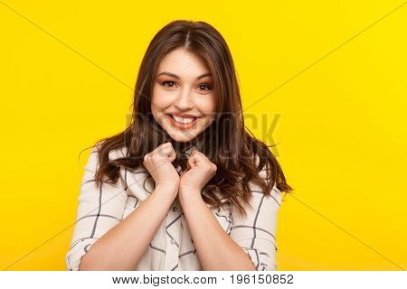 Young girl in shirt holding hands on chest looking excited on yellow background.