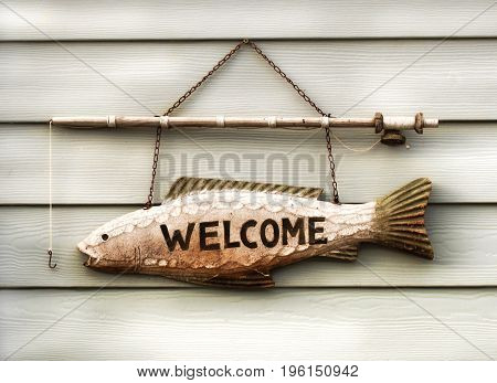 fisherman's welcome sign outside a boat house