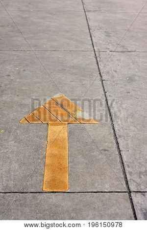 Yellow painted arrow transportation sign on street.