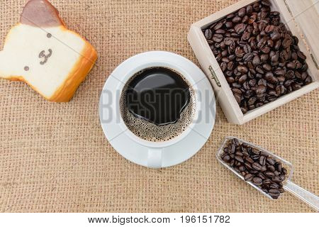 Coffee Cup And Coffee Beans On A Rough Sacking