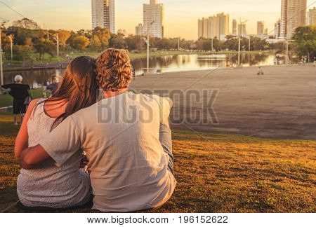 Couple In Love Seated On Grass One Next To Other At Park