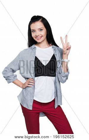 Beautiful Brunette Girl Showing Victory Sign And Smiling At Camera Isolated On White