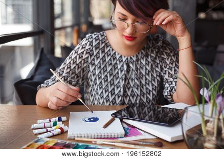 Young pretty girl with glasses sitting in cafe by table and drawing circles in notepad with paints.