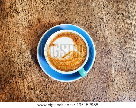 Coffee cup with heart pattern in coffee shop on wooden table with vintage style effect close up with copy space