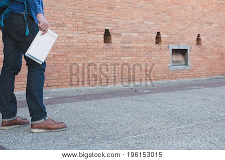 young asian man wearing blue shirt and jeans with map and backpack standing near old orange brick wall