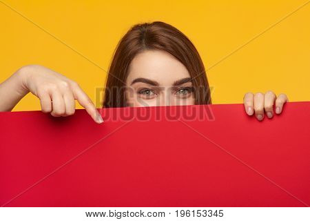 Lovely model holding big sheet of paper behind face and pointing at it on yellow background.