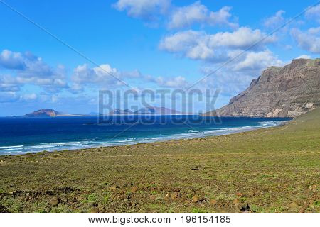 a view of the coast of Caleta de Famara in Lanzarote, Canary Islands, Spain, with the Famara massif to the right and La Graciosa island in the background