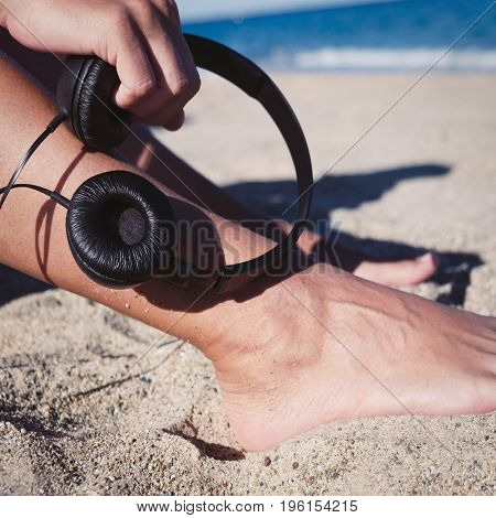 closeup of a young man holding a pair of headphones in his hand sitting in the sand of the beach