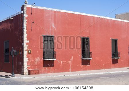 Rustic red old colonial style building with traditional wooden balcony doors on street corner in Valladolid Yucatan Mexico on clear sunny day
