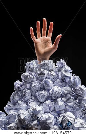 Cropped Shot Of Hand Reaching Out From Heap Of Crumpled Papers Isolated On Black
