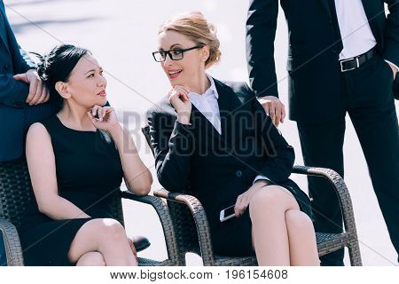 Confident Middle Aged Businesswomen Talking While Sitting On Chairs Between Two Businessmen