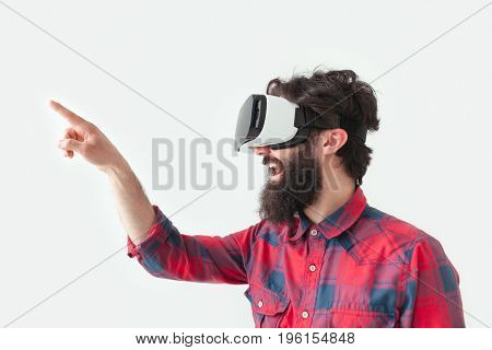 Man pointing with finger wearing the VR helmet. Horizontal studio shot.