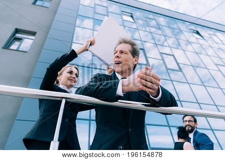 excited mature businesswoman holding folder and hitting businessman outside office building