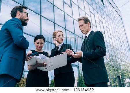 Professional Group Of Multiethnic Businesspeople Discussing Papers Near Modern Office Building