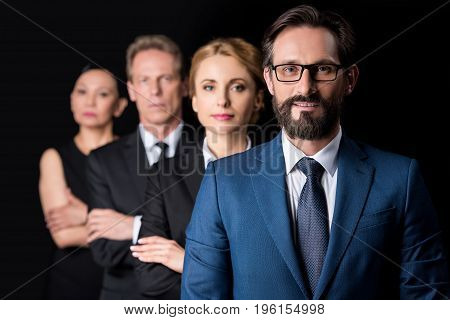 Confident Middle Aged Businesspeople Standing With Crossed Arms And Looking At Camera Isolated On Bl
