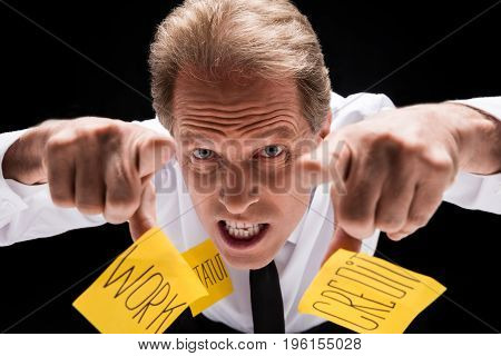 Angry Middle Aged Businessman With Sticky Notes On Clothes Pointing At Camera Isolated On Black