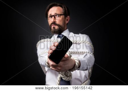 Scared Mature Businessman With Tied Hands Holding Smartphone With Blank Screen Isolated On Black