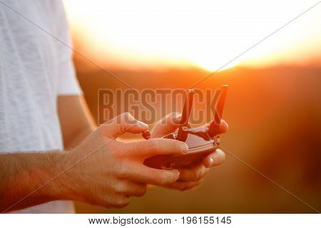 Man holds a drone remote controller in his hands. Close-up of quadcopter RC with antennas during flight. Pilot takes aerial photos and videos with quad