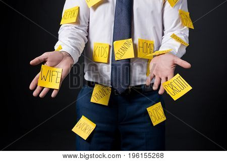 Cropped Shot Of Stressed Businessman With Sticky Notes On Clothes Standing Isolated On Black