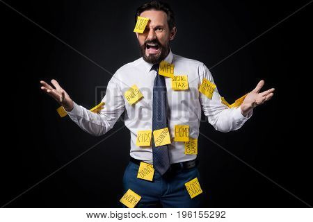 Angry Bearded Businessman With Sticky Notes On Clothes Gesturing  Isolated On Black
