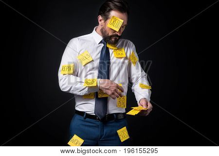 Overworked Bearded Businessman With Sticky Notes On Clothes Standing Isolated On Black