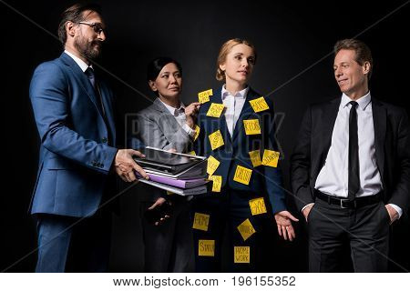 Overworked Middle Aged Businesswoman With Sticky Notes On Clothes Holding Smartphone While Standing