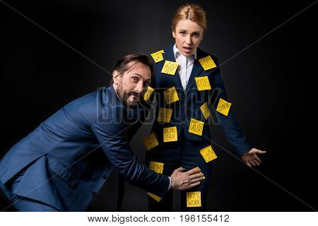 Excited Bearded Businessman Touching Frustrated Businesswoman With Sticky Notes On Clothes Looking A