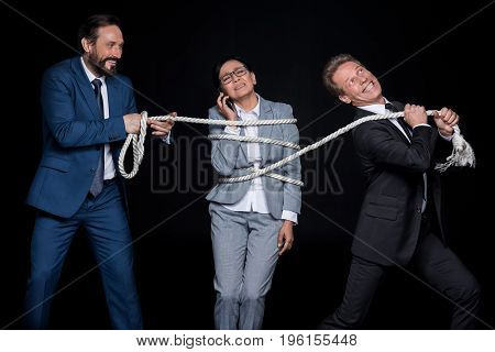Smiling Businessmen With Rope  Tying Mature Scared Asian Businesswoman Talking On Smartphone Isolate