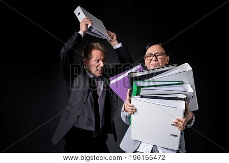 Overworked Mature Businesswoman Holding Folders While Angry Male Colleague Able To Hit Isolated On B