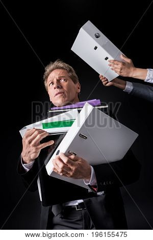 Scared Overworked Mature Businessman Holding Pile Of Folders Isolated On Black